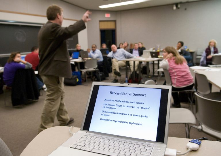 professor stands in front of class teaching with laptop in the foreground